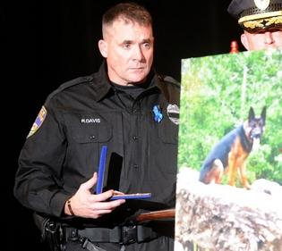 Canton Police Officer Ryan Davis holds a fallen officer medal given to him for his K-9 partner, Jethro during a memorial service last week at Canton Memorial Civic Center. Photo Curtesy of CantonRep.com/ Julie Vennitti
